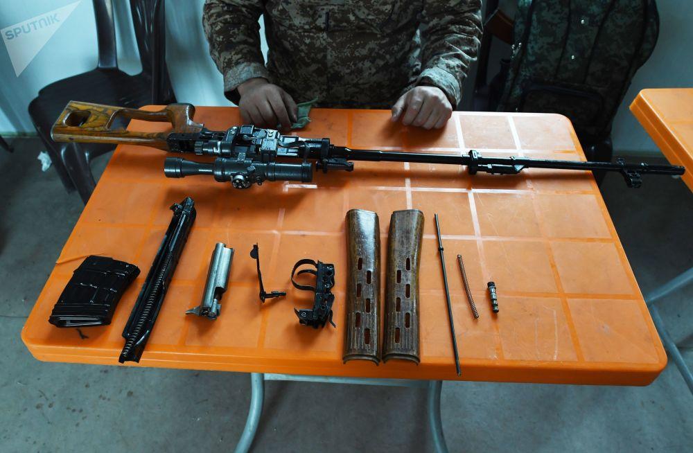 Desmontagem e limpeza de armas após sessões de treinamento de tiro conduzidas por especialistas russos para militares da Síria