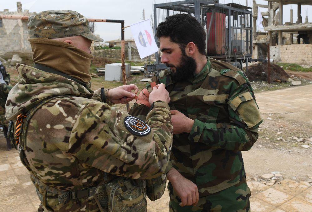 Especialista militar russo junto com um soldado sírio durante a aula de medicina tática em campo de treinamento na Síria