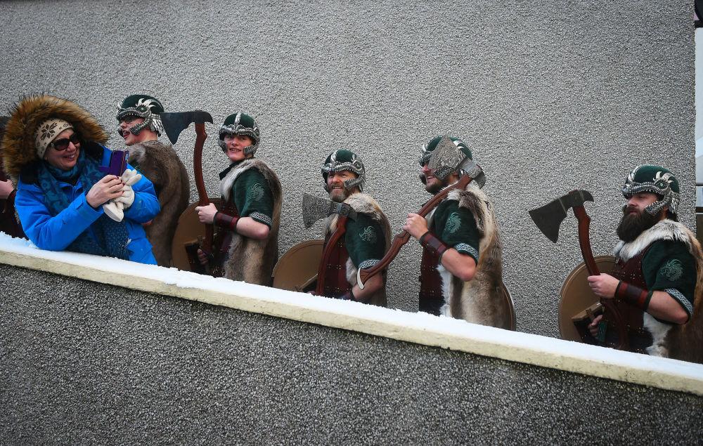 Mulher fotografa participantes vestidos de vikings enquanto se preparam para desfilar pelas ruas de Lerwick, na Escócia, 29 de janeiro de 2019