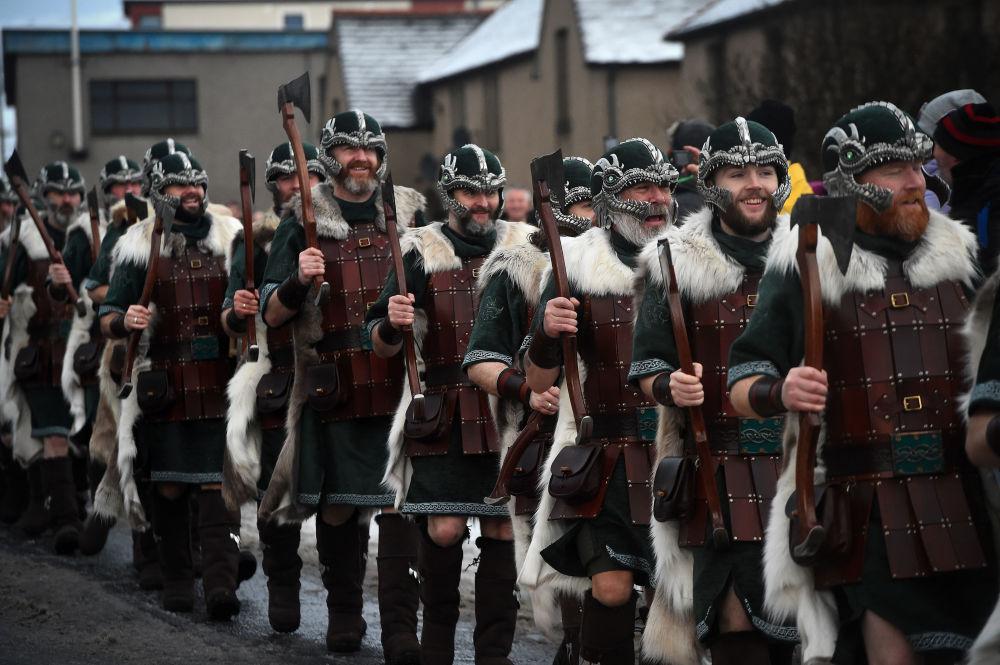 Participantes do festival Up Helly Aa, vestidos de vikings, desfilam pelas ruas de Lerwick, na Escócia, em 29 de janeiro de 2019
