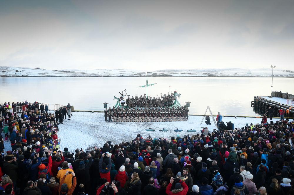 Membros do festival Up Helly Aa, apresentam-se dentro de barco viking na Escócia, em 29 de janeiro de 2019