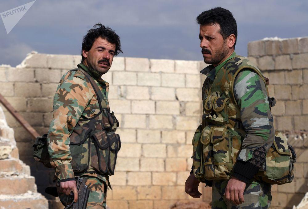 Dois militares conversam durante exercícios na cidade de Manbij