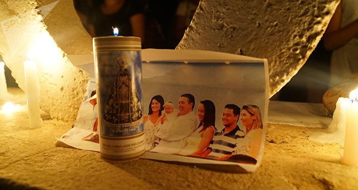 Família é vista em foto colocada sob uma vela no memorial criado por moradores na entrada de Brumadinho, MG.