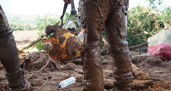 No detalhe, o capacete coberto de lama de uma oficial dos Bombeiros que trata na busca por corpos em Brumadinho, MG.
