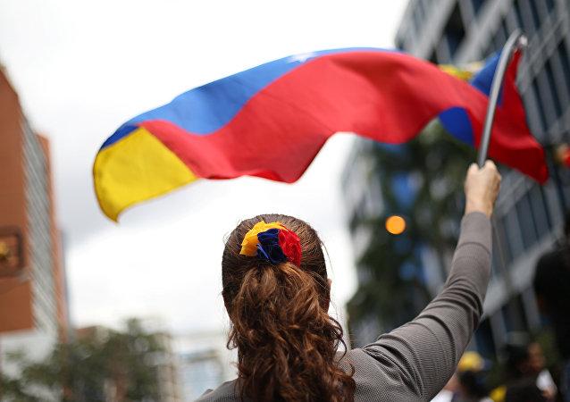 Uma manifestante venezuelana com a bandeira nacional