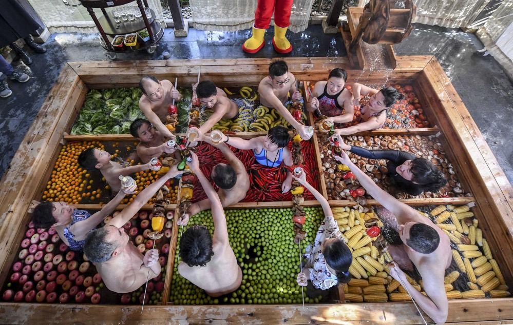 Hóspedes de um hotel na cidade chinesa de Hangzhou passam tempo na piscina quente cheia de frutas e vegetais nas vésperas do Ano Novo Chinês