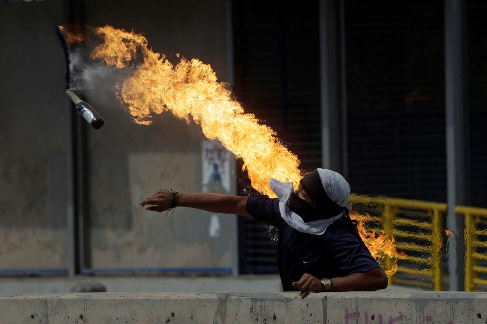 Manifestante joga coquetel molotov durante protestos contra o presidente das Honduras, Juan Orlando Hernandez, em Tegucigalpa