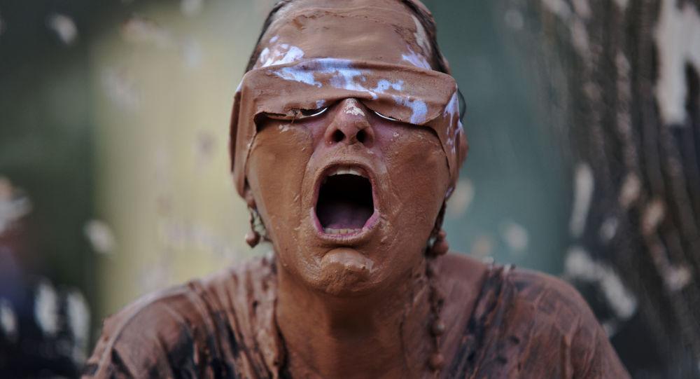 Garota, suja de lama, durante manifestação perante a sede da mineradora brasileira Vale, no Rio de Janeiro