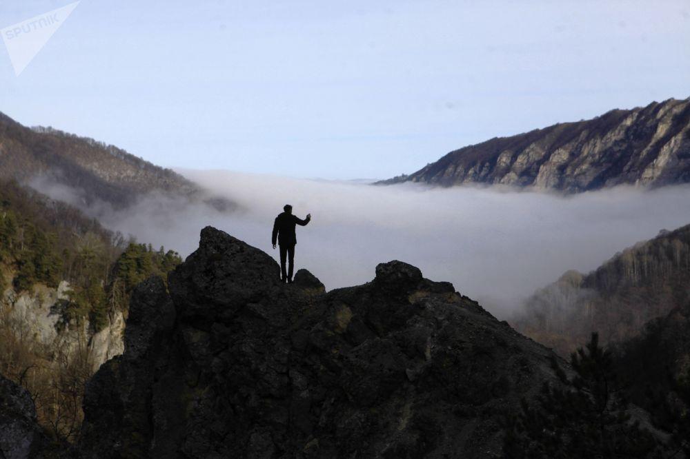 Turista tira foto da neblina nas montanhas da república da Chechênia, Rússia