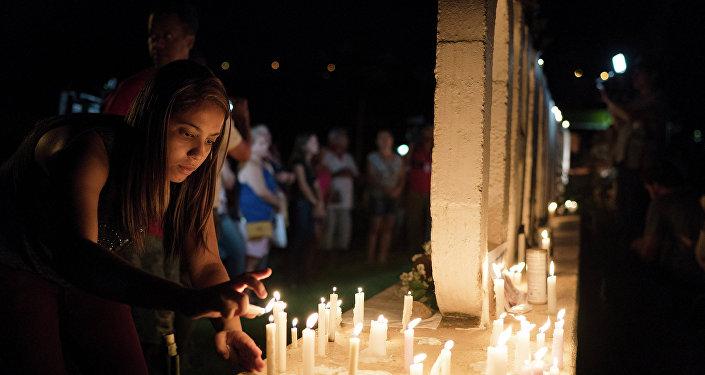 Mulher colocando velas em homenagem às vítimas em Brumadinho (MG).