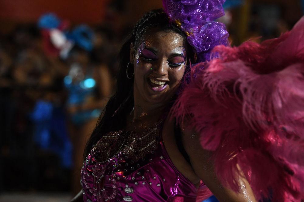 Uruguaia vestindo traje carnavalesco repleto de penas ao ritmo do candombe, em 7 de fevereiro de 2019