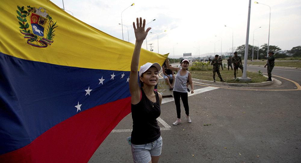Mulher grita bem-vinda ajuda humanitária, balançando bandeira venezuelana em frente a grupo de soldados do Exército venezuelano e oficiais da Guarda Nacional bloqueando o acesso principal à ponte internacional Tienditas, que liga Colômbia e Venezuela, 7 de fevereiro de 2019