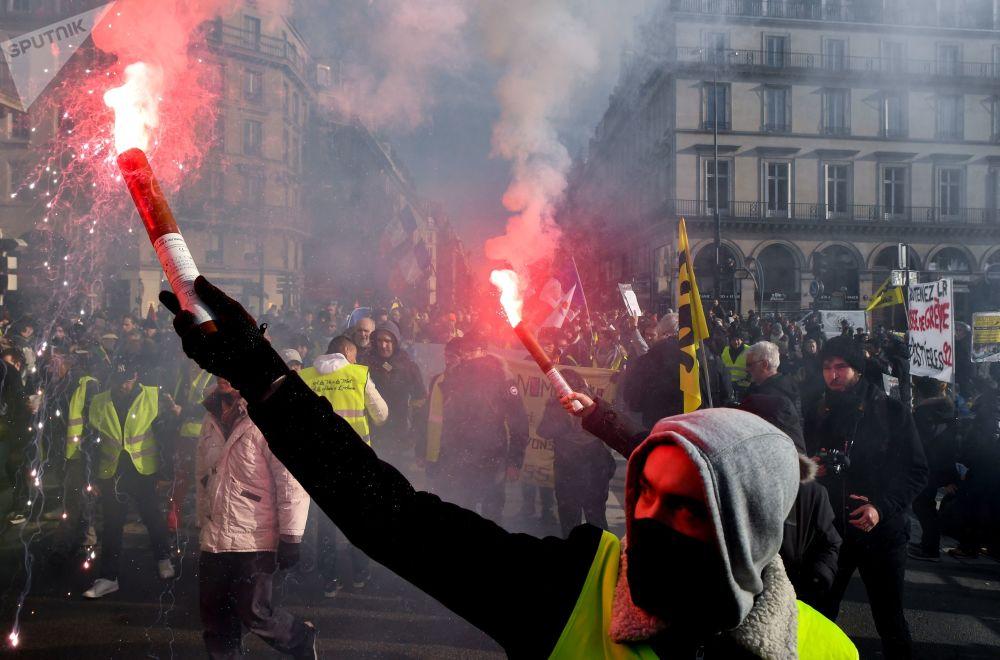 Manifestantes queimam sinalizadores enquanto participam de greve para exigir melhores salários e pensões em Paris, na França