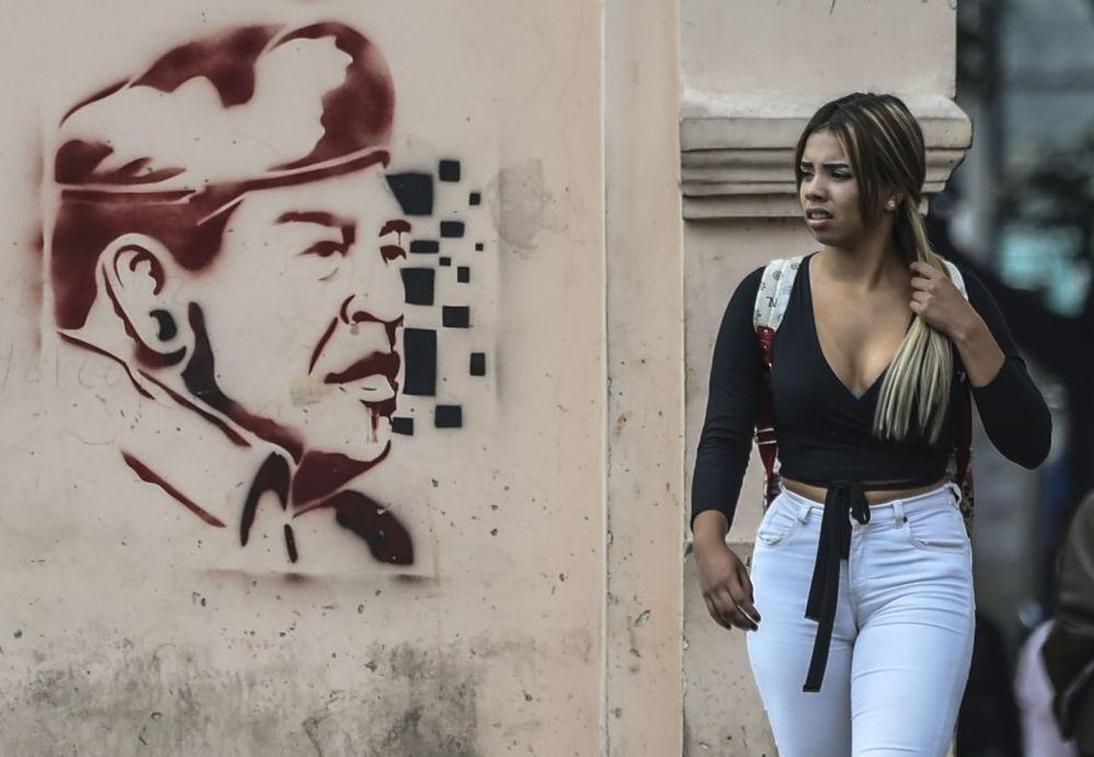Mulher passa por muro com pichação do ex-presidente venezuelano Hugo Chávez, em Caracas, Venezuela, em 6 de fevereiro de 2019