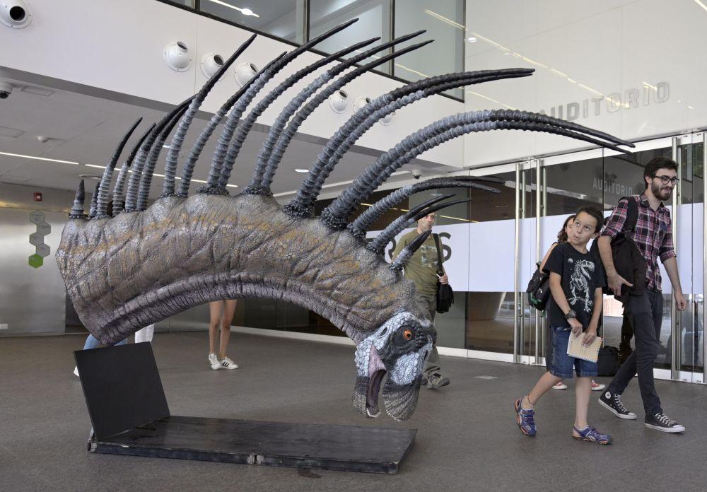 Pessoas passam por réplica do Bajadasaurus pronuspinax, o novo dinossauro encontrado na Patagônia, durante sua apresentação em Buenos Aires, Argentina, em 4 de fevereiro de 2019
