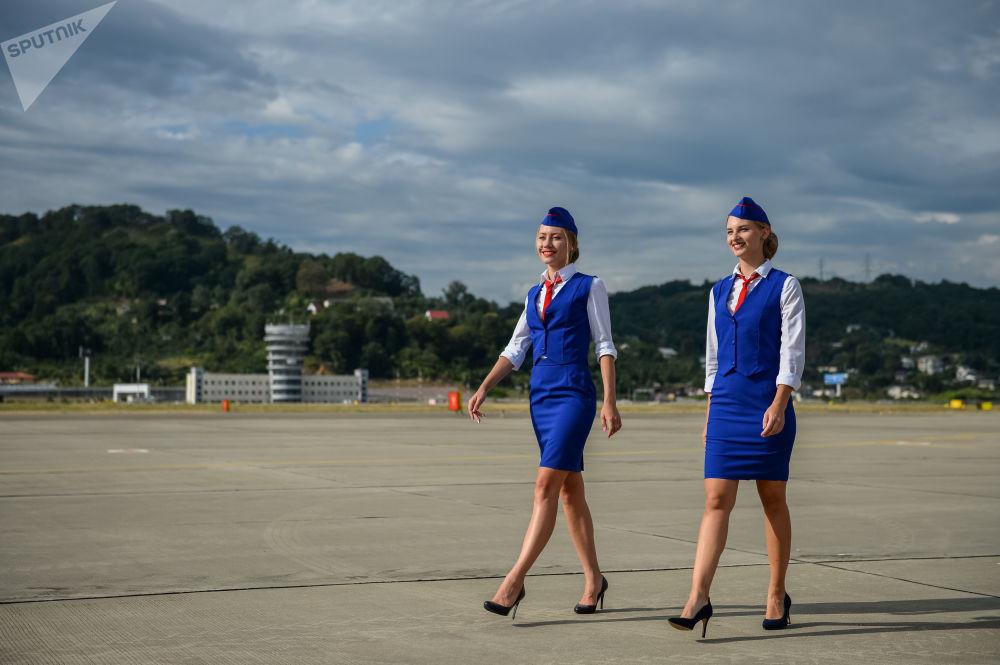 Aeromoças russas caminham pela pista no aeroporto de Sochi