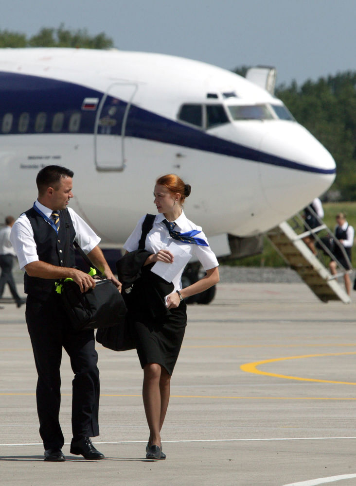 Tripulantes de avião conversam caminhando pela pista no aeroporto de Kaliningrado