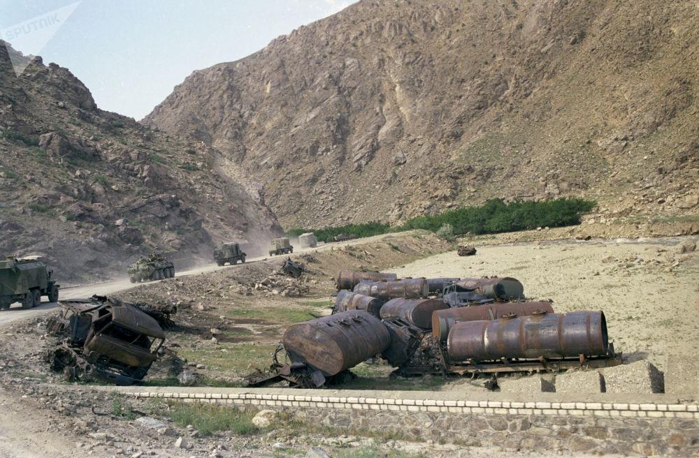 Na beira da estrada há destroços de veículos soviéticos destruídos por rebeldes afegãos