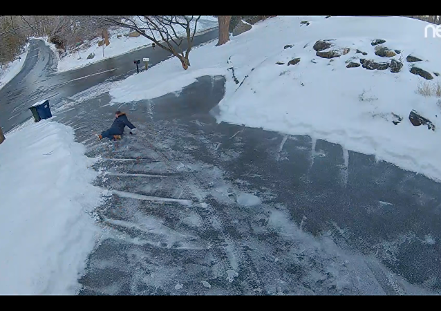 Homem desce a rua escorregando na neve