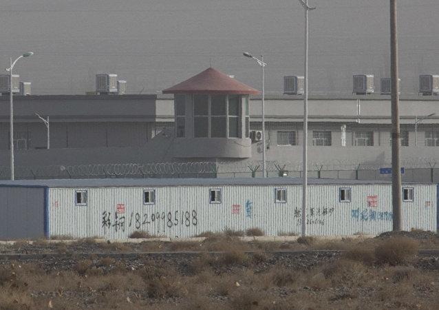Torre de guarda e cercas de arame farpado ao redor de uma instalação no Parque Industrial de Kunshan em Artux, região de Xinjiang, um dos crescentes campos de concentração na região. Estima-se que 1 milhão de muçulmanos foram detidos, sujeitos a doutrinação política, forçados a desistir da língua materna e religião.