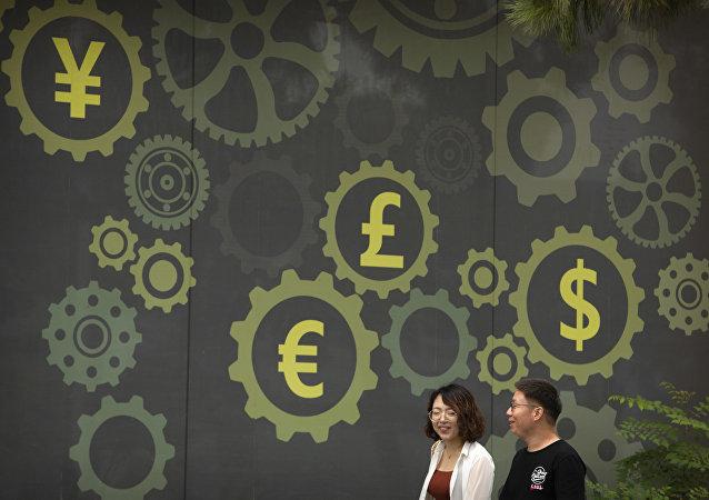 Pessoas caminham em frente a um mural de um banco mostrando símbolos para moedas americana, chinesa, britânica e europeia.