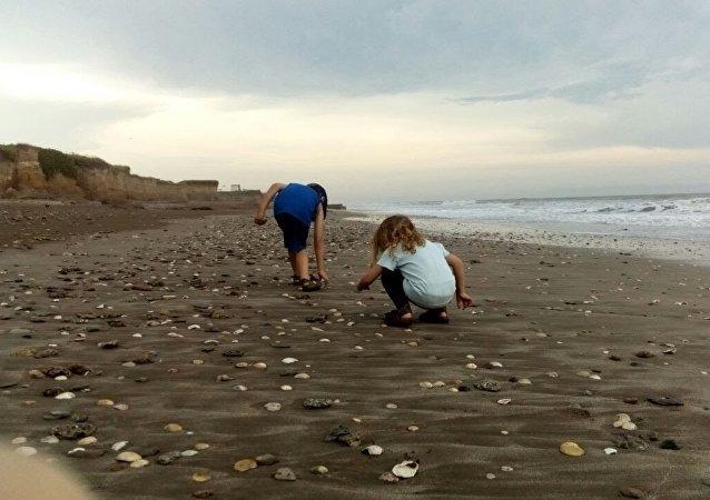 Pequena Indira com seu irmão na praia de Camet Norte, localizada no sudeste da província de Buenos Aires