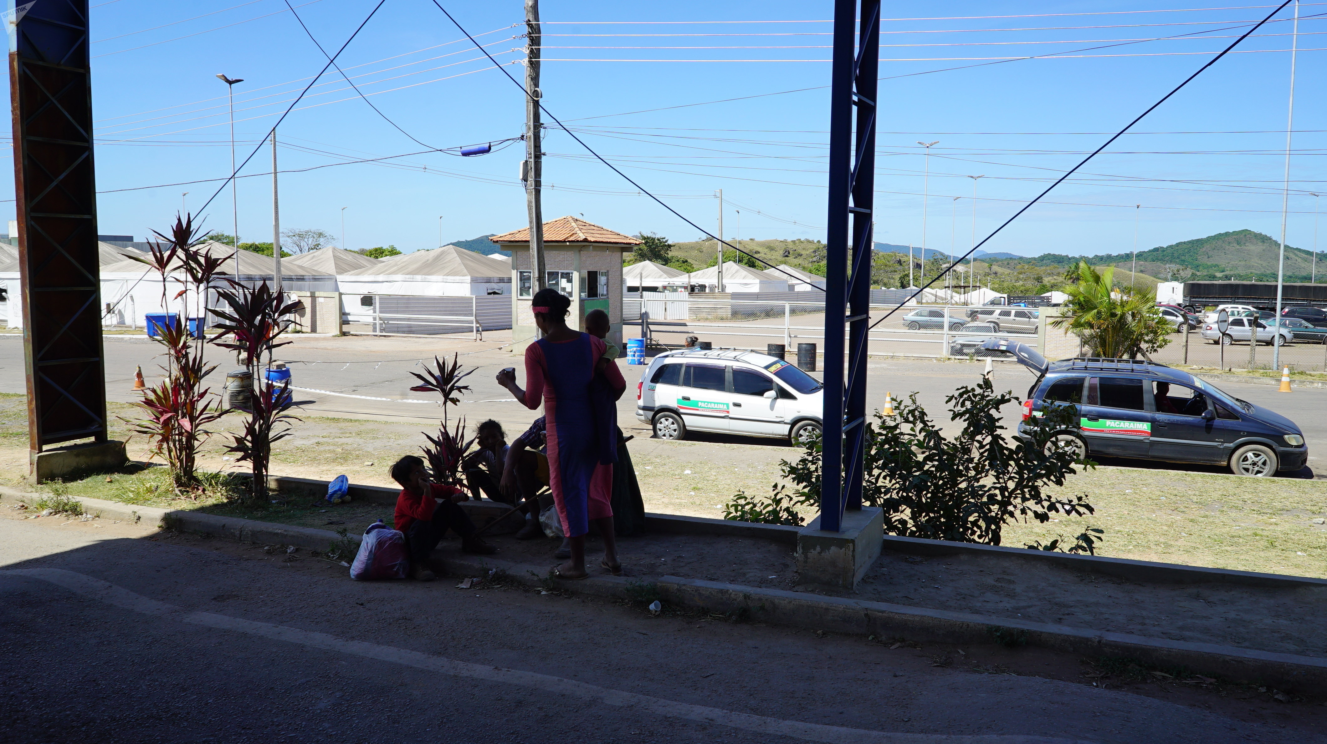 Imigrante venezuelana conversa com seus filhos em frente ao posto de controle da Polícia Federal em Pacaraima