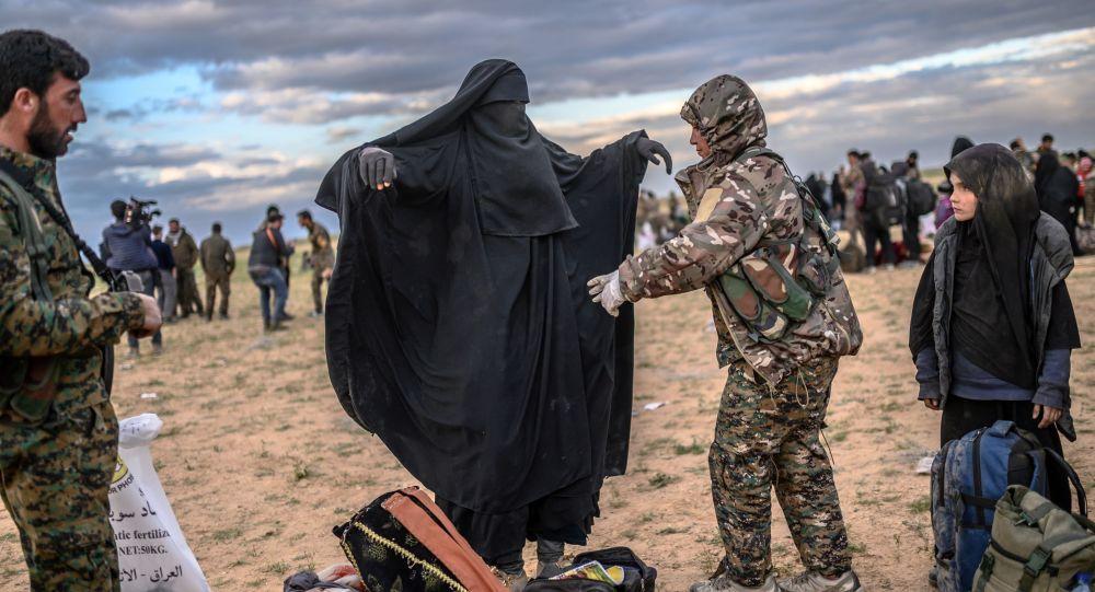 Membro das Forças Democráticas da Síria (SDF), lideradas por curdos, revista mulher em Baghouz, no norte da Síria, em 27 de fevereiro de 2019