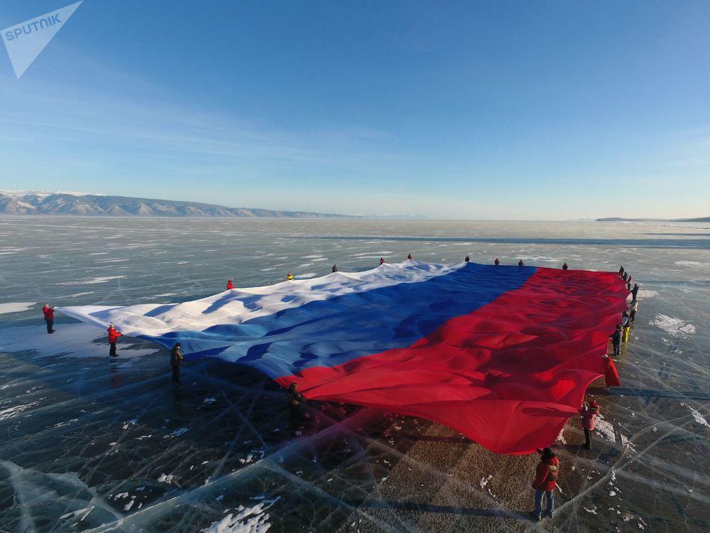 Bandeira nacional da Rússia, com área de 1.423 metros quadrados, estendida sobre o gelo do maior reservatório de água doce do mundo, o lago Baikal
