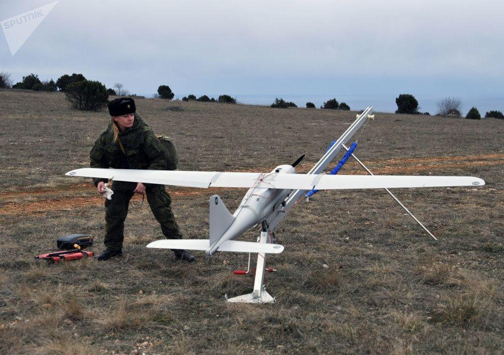 Uma engenheira técnica da unidade feminina especializada em pilotagem de drones se prepara para o lançamento do Orlan-10