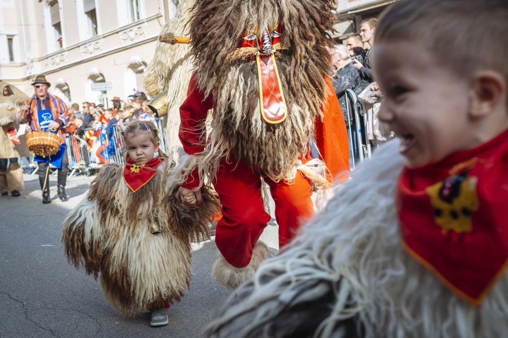 Crianças vestidas como tradicionais personagens etnográficos eslovenos se apresentam durante carnaval na cidade de Ptuj, Eslovênia, em 3 de março de 2019