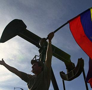 Manifestante da oposição agita bandeira venezuelana em frente aos escritórios administrativos da petroleira estatal venezuelana PDVSA, em Caracas