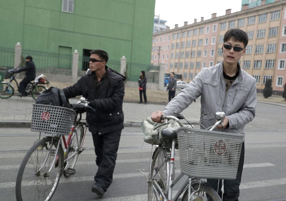 Homens com bicicletas em Pyongyang