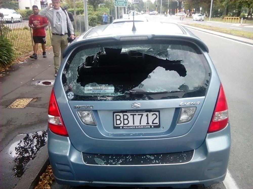 Um homem telefona ao lado de um carro com janelas estilhaçadas perto da mesquita Al Noor depois do tiroteio na cidade neozelandesa de Christchurch