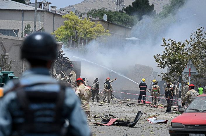 Policial afegão observa resgatistas trabalhando no local de uma explosão no parlamento em Cabul