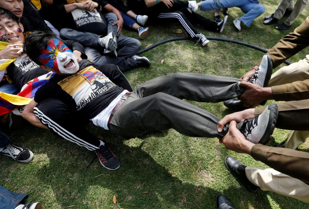 Policiais realizam detenção de participante da manifestação em honra do 60º aniversário da sublevação tibetana contra as autoridades chinesas junto da embaixada chinesa em Nova Deli