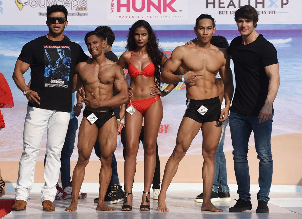 Ator e fisiculturista indiano Sahil Khan e fisiculturista e modelo fitness americano Jeff Seid no palco com participantes do carnaval de corpos praieiros Body Power Beach Show
