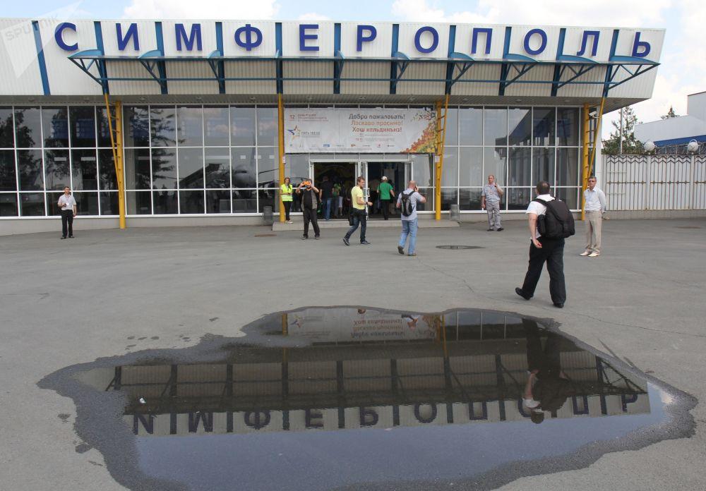 Passageiros perto da entrada do Aeroporto Internacional de Simferopol