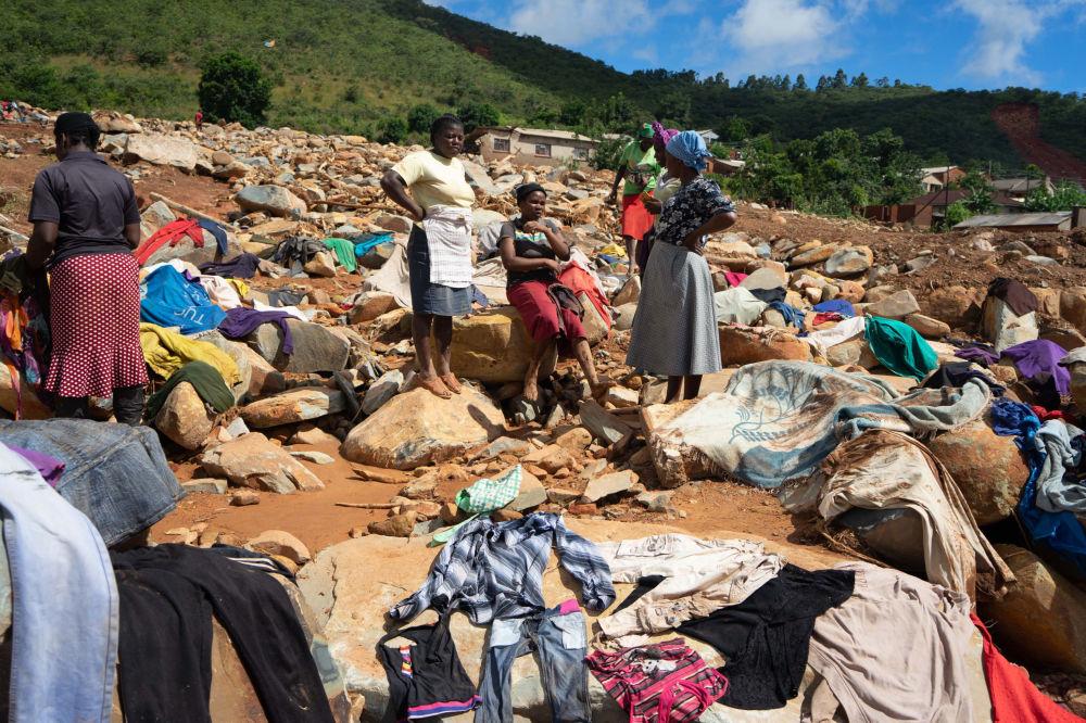 Mulheres secam roupas recuperadas dos escombros em um povoado de Zimbabué