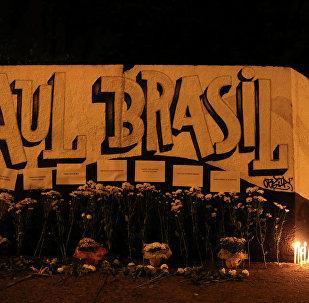 Mulher coloca vela em frente a Escola Estadual Raul Brasil, em Suzano, Grande São Paulo, palco do atentado que deixou 10 pessoas mortas