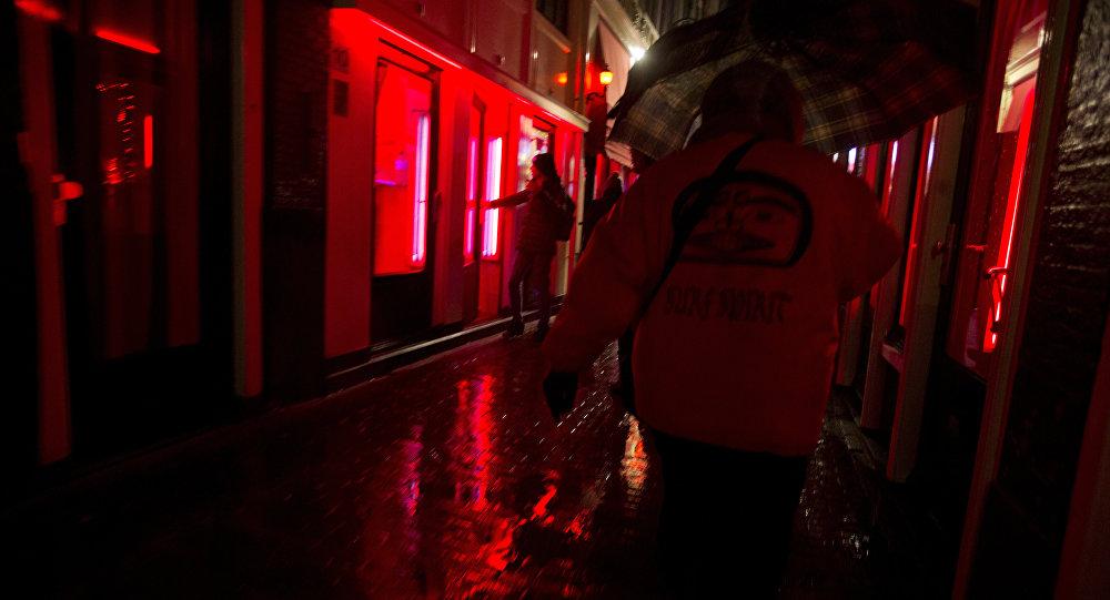 Caminham pelo distrito da luz vermelha em Amsterdã, Países Baixos.