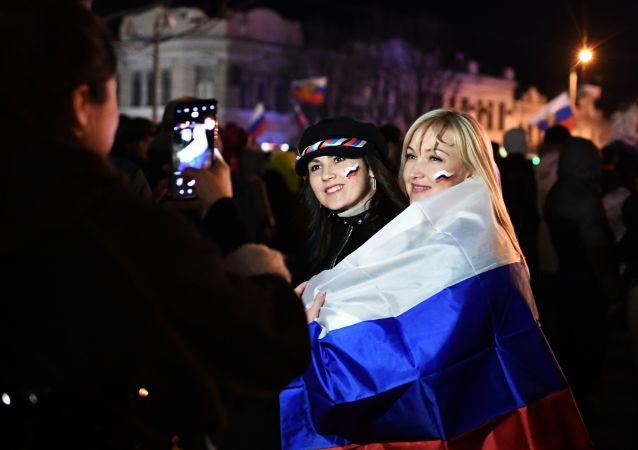 Espectadores tiram fotos no concerto em honra do 5º aniversário da reintegração da Crimeia à Rússia