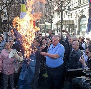 Vojislav Seselj, líder do Partido Radical Sérvio, segura bandeira da OTAN em chamas durante manifestação em Belgrado