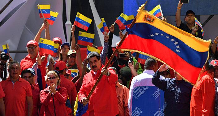 O presidente venezuelano Nicolás Maduro agita a bandeira nacional durante uma marcha pró-governamental em Caracas, em 23 de fevereiro de 2019.