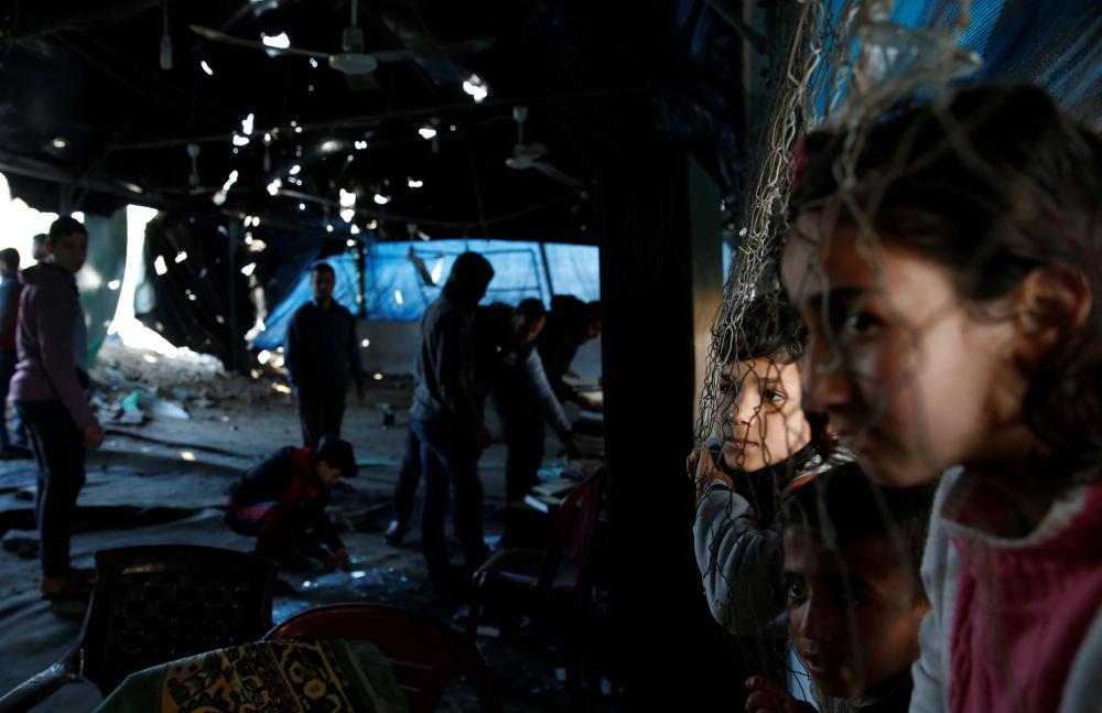 Crianças palestinas observando a inspeção de uma mesquita, atingida pelo mais recente ataque de Israel a Gaza