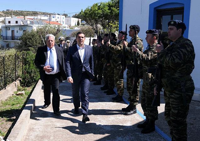 O primeiro-ministro grego, Alexis Tsipras, e o prefeito de Agathonisi, Evangelos Kottoros, avaliam guarda de honra durante uma visita à ilha de Agathonisi, na Grécia.