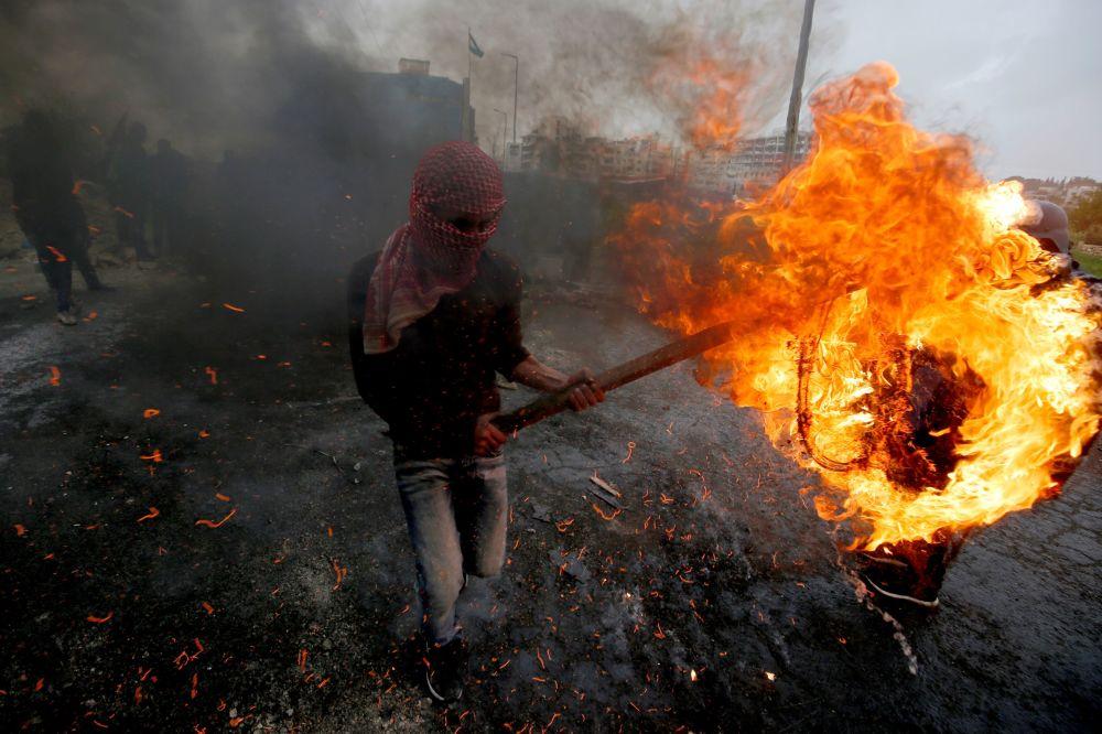 Palestino segura pneu em chamas durantes confrontos com forças israelenses