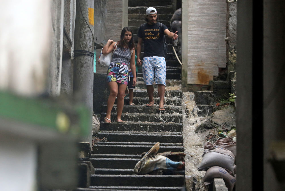 Pessoas descem as escadas em área alagada no Rio de Janeiro