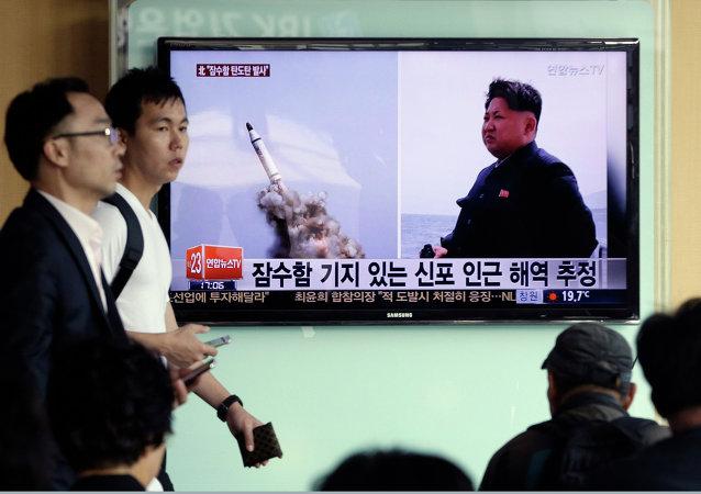 Programa de TV na Coreia do Sul mostra images veiculadas pelo jornal norte-coreano Rodong Sinmun do suposto lançamento submarino de um míssil balístico da Coreia do Norte, ao lado do líder norte-coreano Kim Jong-un, em 9 de maio de 2015