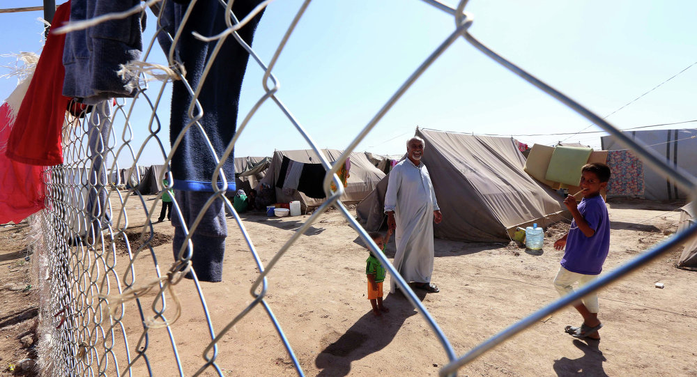 Displaced Iraqis, who had fled their homes after an offensive led by the Islamic State (IS) jihadist group, gather near tents provided by the United Nations High Commission for Refugees (UNHCR) at the Ayden camp, an extension of the larger Aliama camp, in the town of Khanaqin, 160 kms northeast of Baghdad, on September 27, 2014